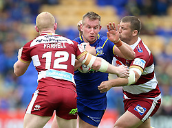 Warrington Wolves Mike Cooper is tackled by Wigan Warriors Liam Farrell (left) and Tony Clubb (right) during the Ladbrokes Challenge Cup, quarter final match at the Halliwell Jones Stadium, Warrington.