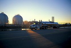 Liquid transport truck parked in front of a refinery and storage facility at sunset