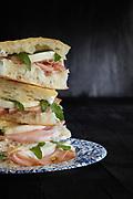 Sandwich with white pizza, mortadella, mozzarella cheese and arugula on black background.