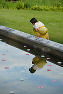 Old Westbury, New York, U.S. - June 21, 2014 - Nikolas Scheiber-Loeis, a member of Young Duncan Dancers, looks at his reflection in the Reflecting Pool with water lilies, before the start of Lori Belilove & The Isadora Duncan Dance Company dancing throughout the gardens during the Midsummer Night event at the Long Island Gold Coast estate of Old Westbury Gardens on the first day of summer, the summer solstice.