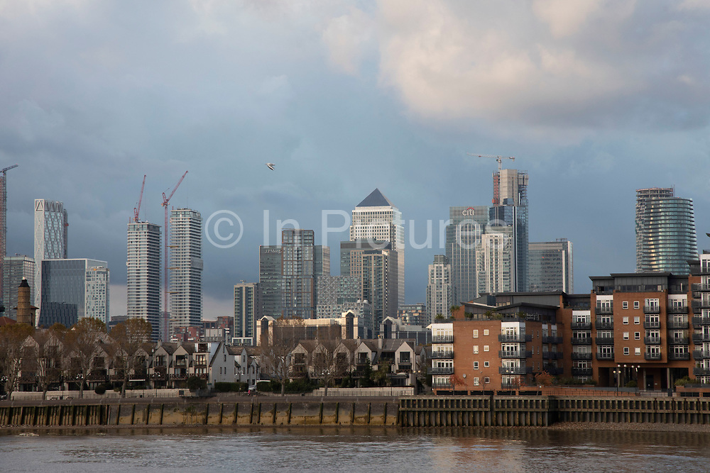 View looking across the River Thames towards Canary Wharf and the Docklands financial district on 5th November 2019 in London, England, United Kingdom. Canary Wharf is the secondary central business district of London and is situated on the Isle of Dogs. It is one of the main financial centres in the world, containing many of the tallest buildings, including the second-tallest in the UK, One Canada Square.
