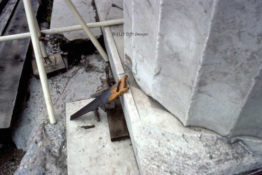 Acropolis, Propylaea, Detail of saw leaning against the base of a Propylon column.  The column flutes are clearly delineated, as it the fact that it has shifted on the platform.