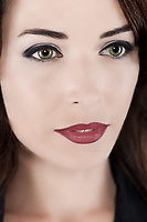 Closeup portrait of a thoughtful beautiful woman with green eyes and red lips