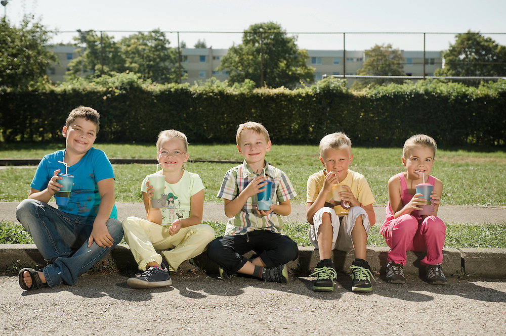 Children with mugs sitting together at curb