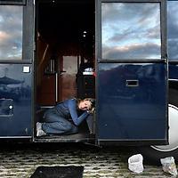 Nederland, Amsterdam , 1 oktober 2014.<br /> De rij caravans met mensen die een zelfbouwkavel willen kopen op het Zeeburgereiland wordt steeds groter.<br /> Sommige staan al een paar weken in de wachtrij totdat ze een kavel mogen kopen. Pas volgende week zaterdag gaan de kavels pas in de verkoop, maar wie weg gaat, verliest zijn plek in de rij.<br /> Een van de kampeerders staat er al een tijdje in zijn caravan: 'Ik ben hier behoorlijk vroeg gaan staan, want er is één kavel waar ik echt geïntresseerd in ben. Er hoeft er maar een eerder te zijn en dan ben je 'm kwijt.'<br /> De wachtende kopers vinden het best gezellig op het terrein: 'Je ontmoet een soort van je toekomstige buren als het zo doorgaat. Dat geeft een apart campinggevoel en we barbecuen samen.'<br /> Een probleempje, als je weggaat ben je je plek kwijt. 'Als je moet werken moet je zorgen dat er iemand anders op je plek zit. Ik had hier eerst helemaal geen zin in, maar het is toch wel een bizar avontuur.'<br /> Op de foto: een doodvermoeide potentiele kavelkoper slaapt in de deuropening van haar bus.<br /> Foto:Jean-Pierre Jans
