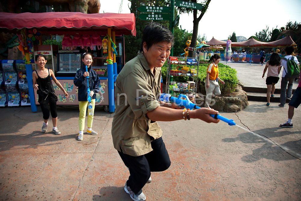 Children having a water fight with water pistols and guns. Soaking wet they are having great fun and laughing as they chase one another. Then, a parent gets involved. Happy Valley Beijing is an amusement park in Beijing, China built and operated by Beijing OTC, which is part of the Shenzhen OCT Holding Group. The park, which is located in the east of Beijing, opened in July, 2006. It is one of four theme parks in the brand chain. Similar in style with the Disney land park, Happy Valley Beijing also featured distinctive landscapes and themes throughout the resort along with featured rides within the different themes. In total there are more than 40 rides.