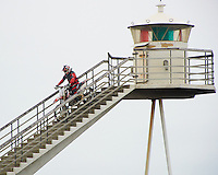 Motocross Rider Descending the Stairway of the Urða Lighthouse. Located on a lava field on the eastern point of Heimaey in Vestmannaeyjar, Iceland. Image taken with a Nikon 1 V2 camera and 10-100 mm VR lens (ISO 160, 100 mm, f/5.6, 1/500 sec). Nikonians Academy Photo Workshop.