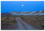 The Full Moon hovers over a Utah landscape near Goblin Valley State Park in the pre-dawn sky, Utah, USA