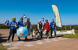 East Lothian, Scotland, United Kingdom, 25th April 2021. Virtual Kilt Walk: Kilt walkers supporting Muirfield Riding Therapy charity cross a 'finish line' to celebrate their participation in their 'Round the World'  fund raising campaign. Each team chose a destination and walked, cycled or rode the miles from home to their chosen point, totalling the 24,900 miles of the earth's circumference and raising over £10,000. Sally Anderson / EdinburghElitemedia.co.uk