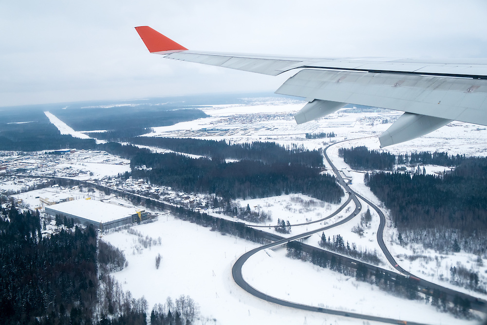 View from an airplane window landing in Moscow during winter time with snow in the ground.