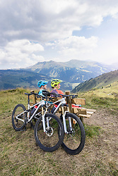 Young couple of mountain bikers sitting on bench in alpine landscape, Zillertal, Tyrol, Austria