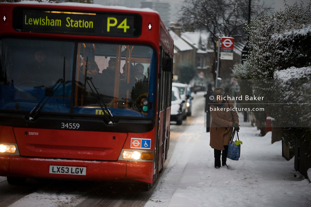 A P4 bus service climbs Herne Hill early after fresh overnight snowfall in the soiuth London area.