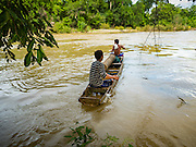 17 JUNE 2016 - DON KHONE, CHAMPASAK, LAOS:  Fishermen push into the channel near Khon Pa Soi Waterfalls, on the east side of Don Khon. It's the smaller of the two waterfalls in Don Khon. Fishermen have constructed an elaborate system of rope bridges over the falls they use to get to the fish traps they set. Fishermen in the area are contending with lower yields and smaller fish, threatening their way of life. The Mekong River is one of the most biodiverse and productive rivers on Earth. It is a global hotspot for freshwater fishes: over 1,000 species have been recorded there, second only to the Amazon. The Mekong River is also the most productive inland fishery in the world. The total harvest of fish from the Mekong is approximately 2.5 million metric tons per year. By some estimates the harvest in the Tonle Sap (in Cambodia) had doubled from 1940 to 1995, but the number of people fishing the in the lake has quadrupled, so the harvest per person is cut in half. There is evidence of over fishing in the Mekong - populations of large fish have shrunk and fishermen are bringing in smaller and smaller fish.        PHOTO BY JACK KURTZ
