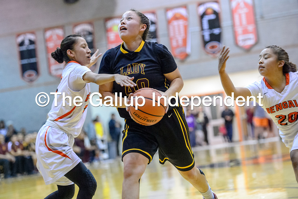 Tohatchi Cougar Samantha Belone (40), center, drives between Gallup Bengals Amanda Mitchell (3), left, and Kamryn Yazzie (20) during the John Lomasney Invitational basketball tournament at Gallup High School Friday.