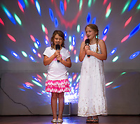 """Molly Hagan and Leanna Rowley sing """"Blank Space"""" on stage during the Holy Trinity School talent show on Tuesday afternoon.  (Karen Bobotas/for the Laconia Daily Sun)"""
