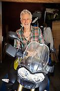 Senior Man Sitting On Motorcycle In Garage