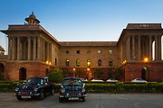 "The Secretariat Building or Central Secretariat is where the Cabinet Secretariat is housed, which administers the Government of India. Built in the 1910s, it is home to some of the most important ministries of the Cabinet of India. Situated on Raisina Hill, New Delhi, the Secretariat buildings are two blocks of symmetrical buildings (North Block and South Block) on opposite sides of the great axis of Rajpath, and flanking the Rashtrapati Bhavan (President's House).<br /> .....<br /> The Secretariat Building was designed by the prominent British architect Herbert Baker in Indo-Saracenic Revival architecture. Both the identical building have four levels, each with about 1,000 rooms, in the inner courtyards to make space for future expansions. In continuation with the Viceroy's House, these buildings also used cream and red Dholpur sandstone from Rajasthan, with the red sandstone forming the base. Together the buildings were designed to form two squares. They have broad corridors between different wings and wide stairways to the four floors and each building is topped by a giant dome, while each wings end with colonnaded balcony.<br /> Much of the building is in classical architectural style, yet it incorporated from Mughal and Rajasthani architecture style and motifs in its architecture. These are visible in the use of Jali, perforated screens, to protect from scorching sun and monsoon rains of India. Another feature of the building is a dome-like structure known as the Chatri, a design unique to India, used in ancient times to give relief to travelers by providing shade from the hot Indian sun.<br /> The style of architecture used in Secretariat Building is unique to Raisina Hill. In front of the main gates on buildings are the four ""dominion columns"", given by Canada, Australia, New Zealand and South Africa. At the time of their unveiling in 1930, India also supposed to become a British dominion soon, however India became independent within the next 17 years and the Secretariat became the"