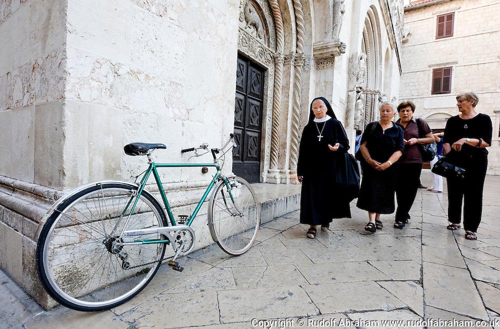 Women and bicycle outside the Cathedral of St Anastasia (Sv Stosija), Zadar, Croatia