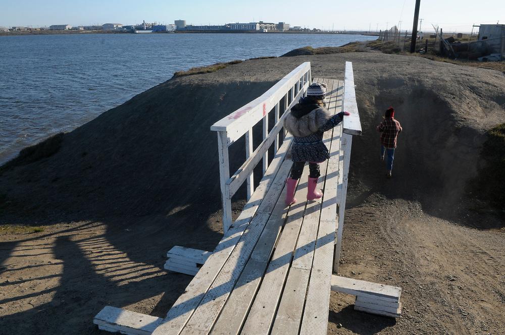 Barrow, Alaska.   Summer vacations in Barrow.children play on the boardwalk over the tundra