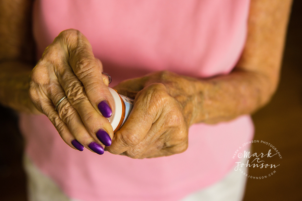 Older woman taking cap off of pill bottle people ****Model Release available