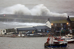© Licensed to London News Pictures. 27/01/2016. Lyme Regis, UK. Workmen  (foreground) brave harsh weather conditions as large waves crash over the Cobb at Lyme Regis harbour in  Dorset, south west England at high tide. The tail end of storm Jonas continues to hit the UK, bringing torrential rain and gales. Photo credit: Peter Macdiarmid/LNP