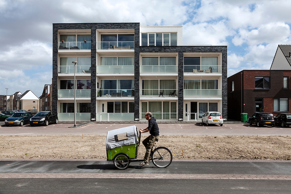 Dutch man on a bakfiets (cargo bike) used to carry children, pets and shopping