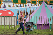 Arriving in the mud is a struggle and a father resorts to carrying his child  - The 2016 Glastonbury Festival, Worthy Farm, Glastonbury.