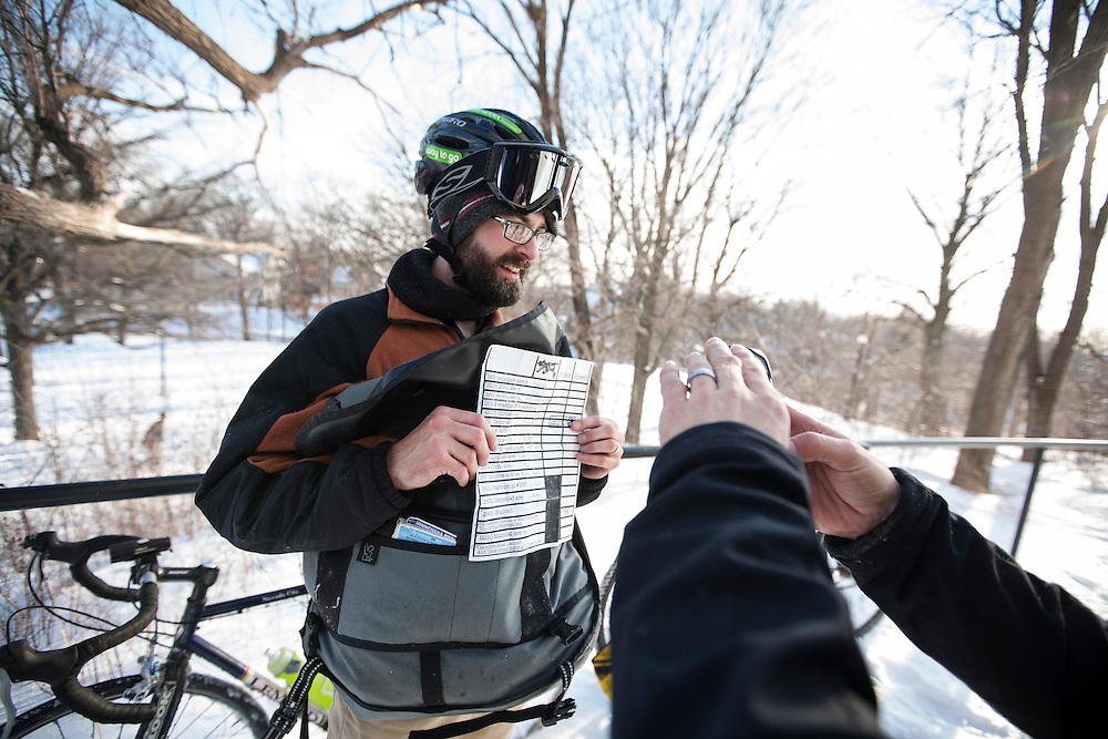 Jonathon Heide has a friend photograph his time card after they officially checked in at Prospect Park during the Stupor Bowl 17 bike race in Minneapolis February 1, 2014.
