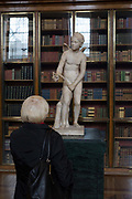 A lady visitor admires a sculpture of Cupid, a 2nd century Roman copy of a Greek original, in the Enlightenment Gallery of the British Museum, on 11th April 2018, in London, England.