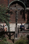Lunchtime Londoners rest in summer sunshine beneath a crucifix in the City of London, UK.