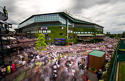 Crowds gather outside centre court as they wait for Roger Federer to parade the trophy on a centre court balcony after beating Marin Cilic in the Gentlemen's Singles Final on day thirteen of the Wimbledon Championships at The All England Lawn Tennis and Croquet Club, Wimbledon.