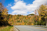 Highway with mountain of Fall color trees and blue sky.