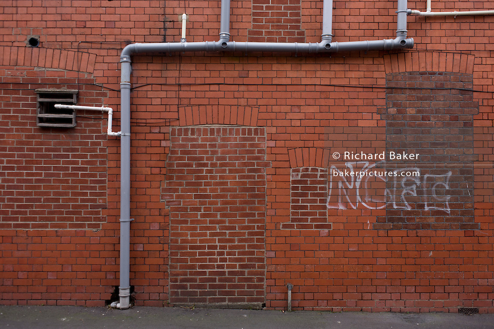 Bricked up doorway and windows with football graffiti in a vacant building during recession in the city of Newport, Wales.