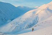 Michelle Blade skins up a hillside at sunset in Koslådalen, Svalbard.