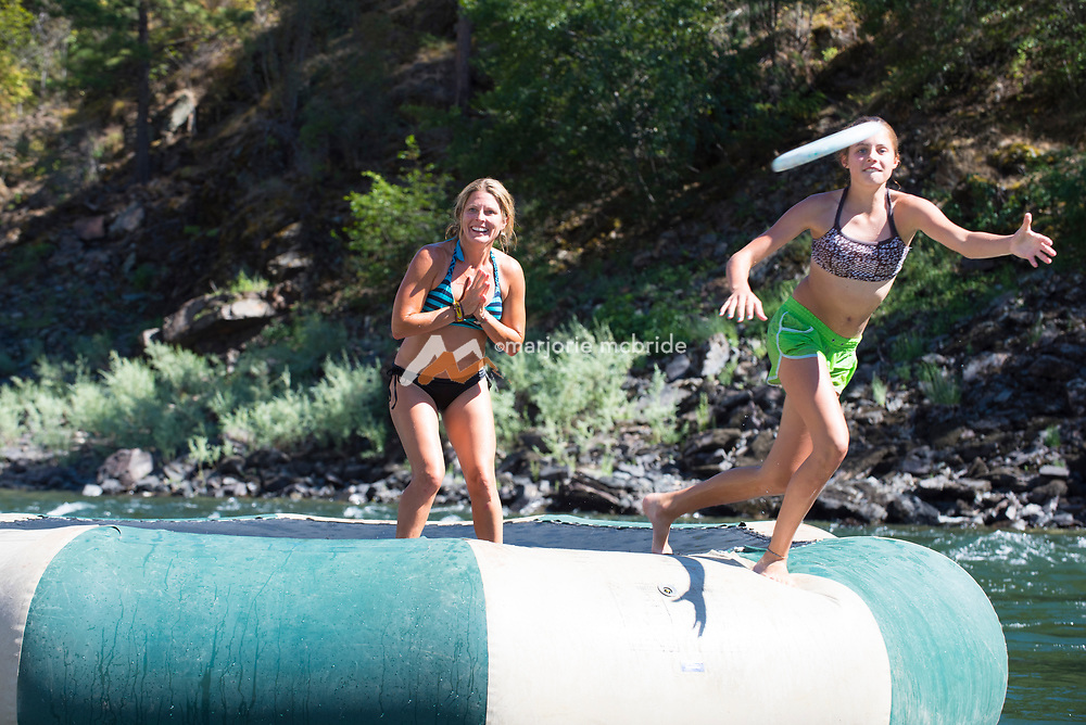 Mother and daugther playing frisbee on a river trampoline during a rafting trip on the Main Lower Salmon River, Hammer Creek to Hellar Bar, Idaho.