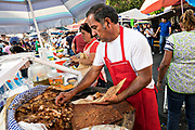 A Mexican butcher chops up freshly barbecued pork carnitas in the town known as the Carnitas Capital of México in Quiroga, Michoacan, Mexico.