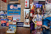 A Latino ad for a Spanish language newspaper and local fashion business at Elephant & Castle, where massive regeneration is due. Next to mannequins wearing east European fashions and styles, we see media adverts from the Spanish-speaking world alongside money transfer companies such as Sigue and corier shippers, Ashley's.