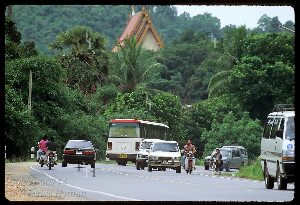 Motorbikes, cars and bus zip along highway past Buddhist shrine on Phuket Island. Thailand