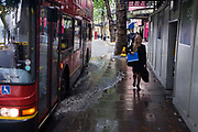 A young woman walking along a London street is about to be splashed by a passing London double-decker bus at a flooded bus stop. After heavy rain that fell over the capital, puddles or filthy water lies in gullies and gutters of the urban streets - including this bus stop in Aldwych. The young woman is aware of the camera and walks in smart office shoes on the wet pavement (sidewalk) as the bus draws to a halt ahead. But she is more self-conscious than taking precaution not to get wet. The moment before her soaking is caught as the water laps across the kerb and into her path. In the background are the West End theatres whose productions attract drama fans from across the world.