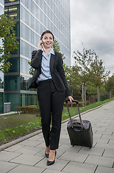 Businesswoman pulling luggage while calling with mobile phone, Bavaria, Germany