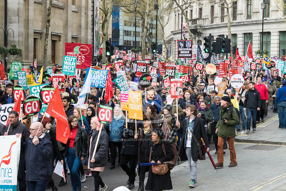 """London, April 16th 2016. Protesters march past St Martin In-the-Fields Church towards Trafalgar Square as thousands of people supported by trade unions and other rights organisations demonstrate against the policies of the Tory government, including austerity and perceived favouring of """"the rich"""" over """"the poor""""."""