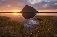 Midnight sun hangs low on the horizon next to Hoven mountain peak, Gimsøy, Lofoten Islands, Norway