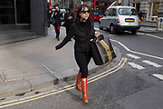 Woman with shopping bags wearing red Hunter boots. London, UK. Hunter Wellington boots, once country wear are now a top fashion item. Wellies on the mainstream highstreet.