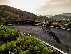 woman riding bike against mountain forest during sunset