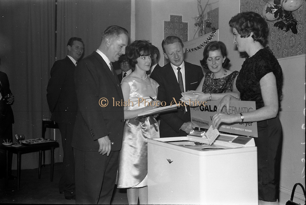 """17/12/1962<br /> 12/17/1962<br /> 17 December 1962<br /> A.E.I. Gala reception at Shangri-la Hotel, Dalkey, Dublin, where a Gala Supermatic washing machine was presented to the Variety Club of Ireland for their Easter Draw by Gala. At the function were Des O'Keefe, Chief Barker, Variety Club of Ireland; Patricia Kavanagh, (Gala Demonstrator); Mr. P.N. Walsh, Area Manager for Ireland; Aine Twomey, (Gala Demonstrator) and Annette Vahey, (Gala Demonstrator) drawing the tickets for the lucky winners in the Gala """"Take your chance"""" promotion for purchasers of Gala products."""