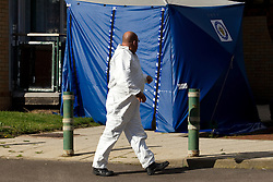 © Licensed to London News Pictures. 06/10/2012. Walsall , UK . A forensic examiner walks in front of a blue tent erected at the scene . Police and forensic examiners investigate after two bodies were found at a block of flats . A woman was found inside a flat in Holly Court , Acacia Avenue , Walsall and a man was found dead outside the block . Photo credit : Joel Goodman/LNP