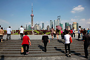 Visitors walk on the Bund with a view of Pudong's modern Lujiazui Financial District across the Huangpu River in Shanghai, China on 05 September, 2011. The Bund and the skyscrapers of Pudong are the most famous and iconic sites of Shanghai.