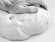"""Hands of a baker kneading dough in a bakery at night. This image was part of a photo exhibition """"Let there be Bread"""" by Oren Shalev in the Eretz Israel Museum in Tel Aviv, Israel. The motif of the exhibition was bread. Such a basic food yet so complex and diverse. The images were produced by following the nightly work at a bakery from start to finish. To view all images from this exhibition please search for breadexhibition"""