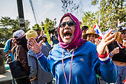 22 DECEMBER 2013 - BANGKOK, THAILAND:  An anti-government protestor screams as she marches past a roadblock blocking the road to the home of Yingluck Shinawatra. Hundreds of thousands of Thais gathered in Bangkok Sunday in a series of protests against the caretaker government of Yingluck Shinawatra. The protests are a continuation of protests that started in early November and have caused the dissolution of the Pheu Thai led government of Yingluck Shinawatra. Protestors congregated at home of Yingluck and launched a series of motorcades that effectively gridlocked the city. Yingluck was not home when protestors picketed her home.    PHOTO BY JACK KURTZ
