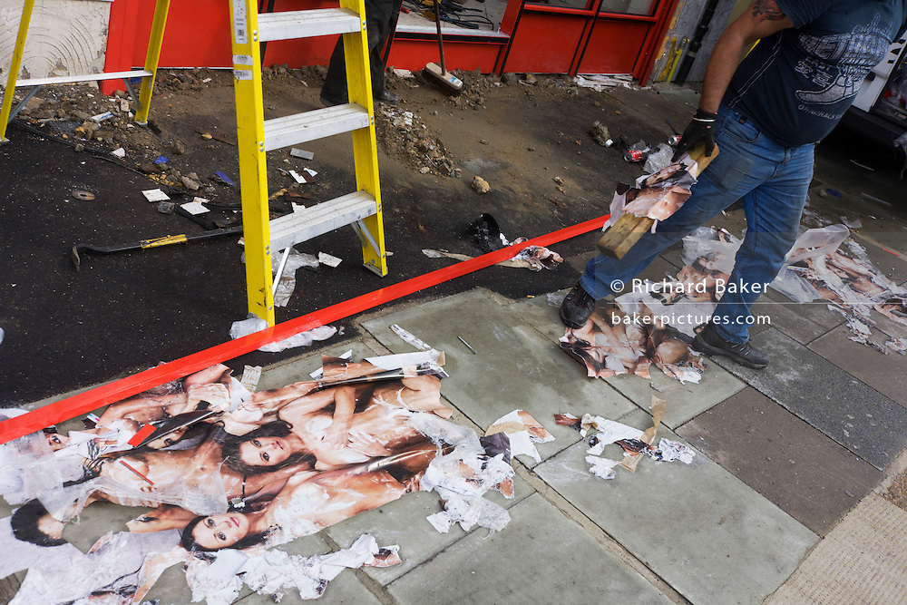 Workmen clear away sexist ad posters lie on a London street after being removed from a refurbished shop construction site.